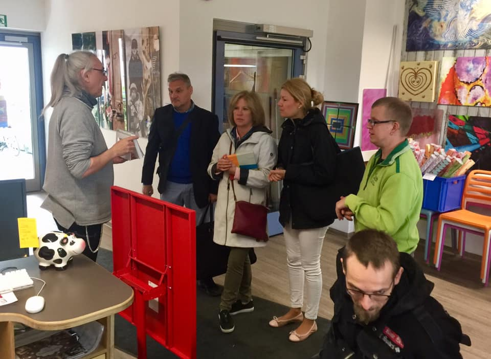 At Art department in Pfennigparade. Teacher explaining the work of the disabled persons. Art pictures on walls.