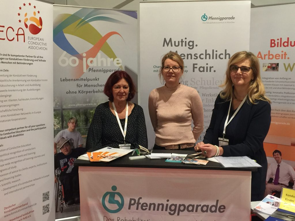 Information Stand with ECA roll-up showing three people of ECA at RehaKind congress in Munich