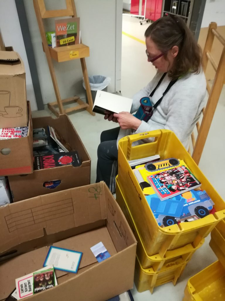 Young adult sitting on Petö chair reading. Boxes with books around her.