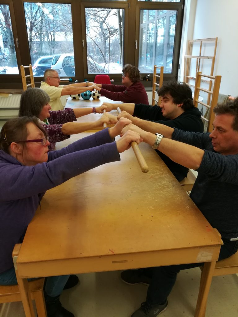During a Conductive Session: Six adults are sitting at a table opposite each other building pairs. Each opposite pair hols onto an excercise stick either side. Everyone sits on Petö Chairs.