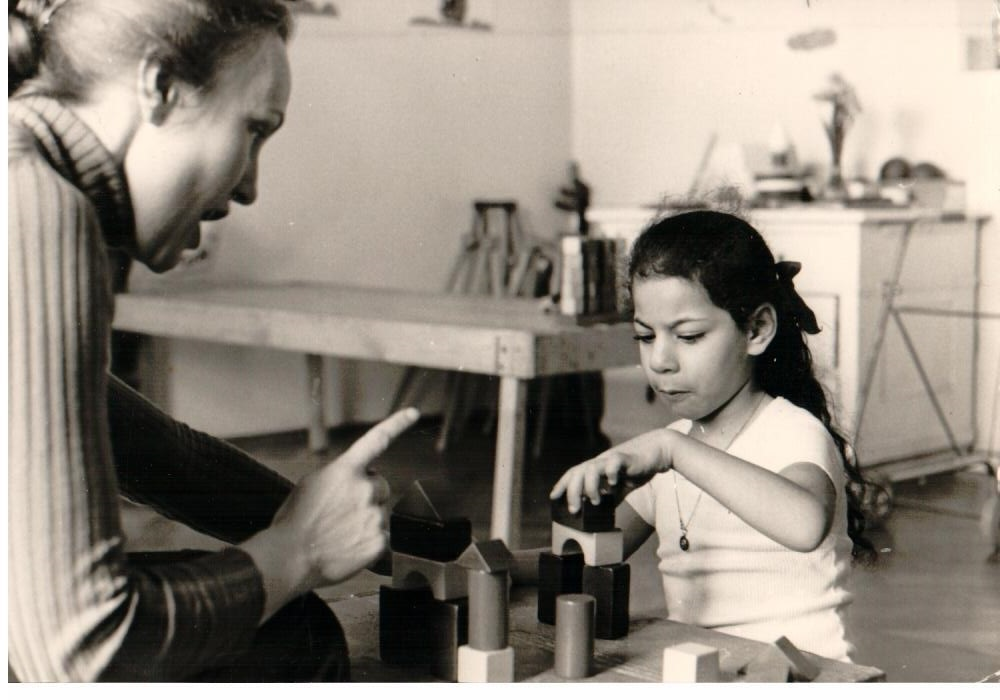 black and white picture. Teacher sitting with child at table talking to the girl, pointing a finger. The girl piles up bricks to a house.