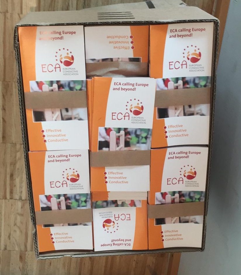 A brown box full with piles of ECA flyers. The flyers have the titel ECA calling Europe and beyond!