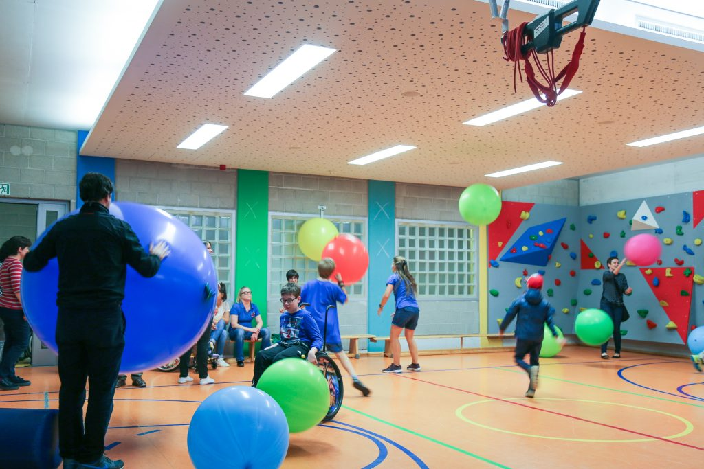 Disabled and non-disabled children, parents and teachers playing with huge colored balls in excercise hall. The balls are bounding up and down.