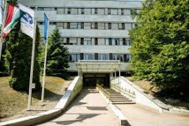 Front Entrance of Semmelweis University building. Three flgas on left. Tree on right. The building has 4 stories. The entry is barrier-free.