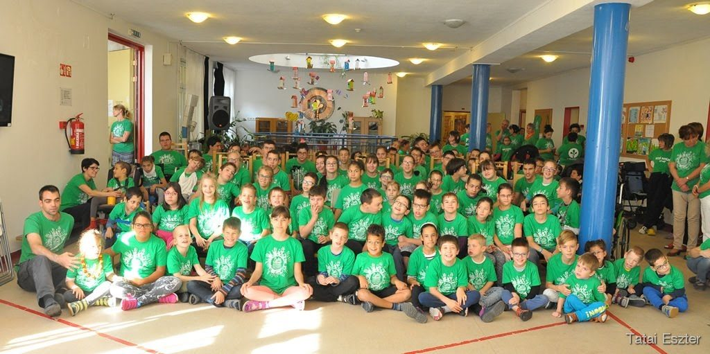 Picture of a group of ca. 30 children all with green t-shirt, sitting on floor of school in Hungary at WCPD.