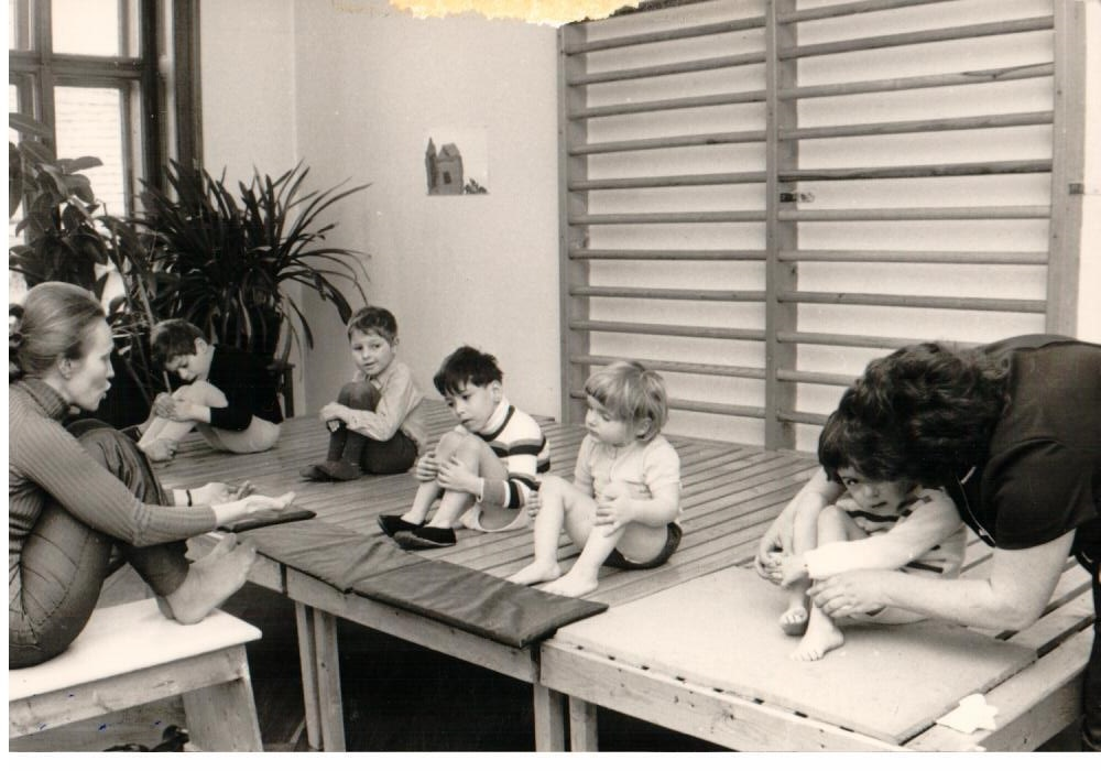 black and white. Children sitting on Petö tables. Teatcher in front of them on a stool explaining what to do next.