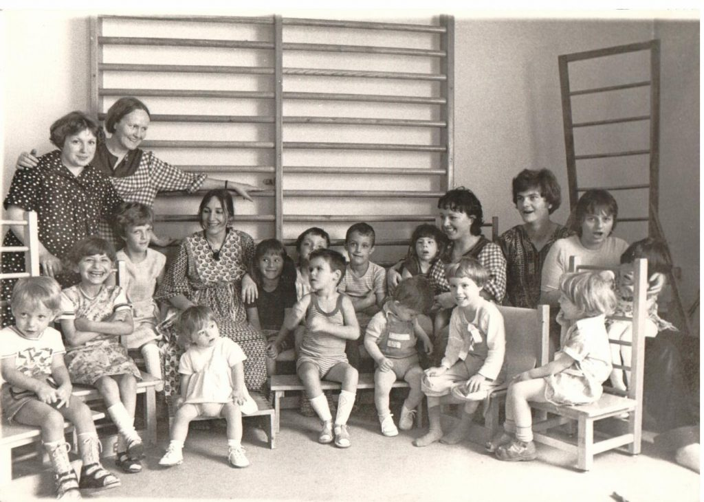 black and white: Children sitting on chairs with teacher. Group picture. In the back ground wall ladders.