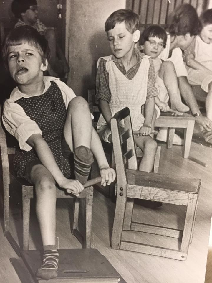 Black, white: small children sitting on wooden chairs during CE excercise. They try to pull their leg up and lift it over a stick which they are holding with two hands.