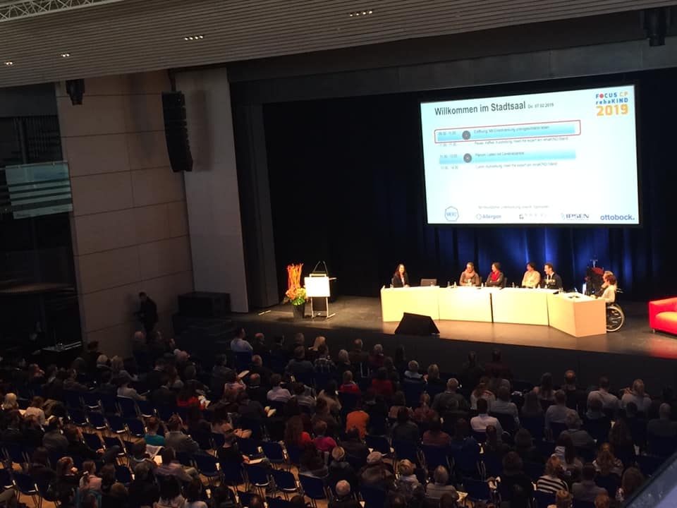 Conference showing audience and stage. On stage podium with 8 people, one person in wheel chair. Background: blue curtain with Slide show saying: Wellcome in the City Hall (Presentation showing in German language)