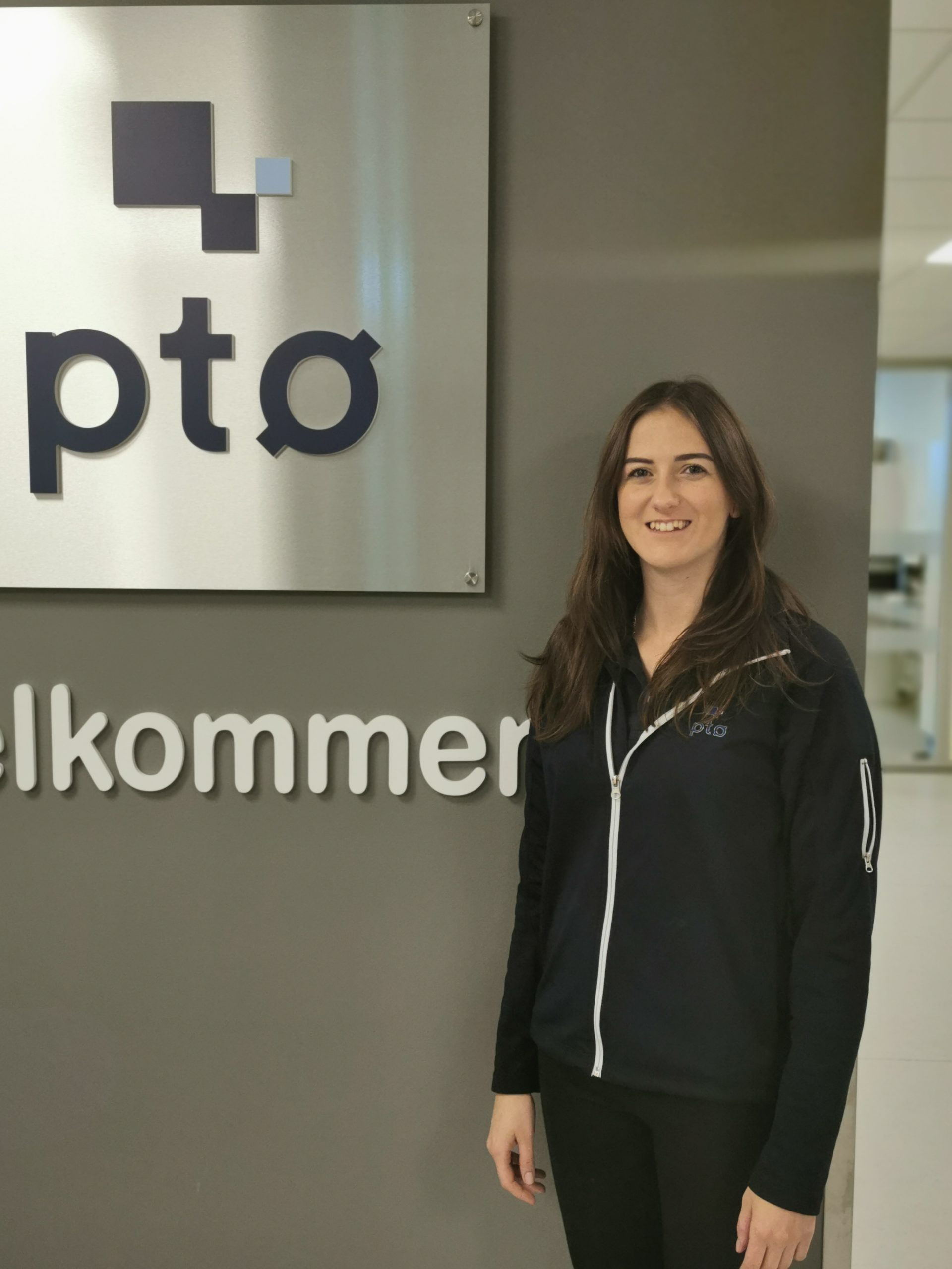 In the picture you see a young conductor with long brown hair on the right, smiling proudly, wearing a black sweat jacket and black trousers. She is standing in front of the PTO Norge logo. The logo shows three different size squares, two of them black, one grey, underneath the small letters pto.